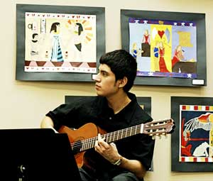 PHOTO: Joy Zelada plays guitar in Orange Hall Gallery