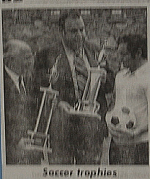 OCCC Soccer Coach Jim Migli receives trophies at the indoor soccer tournament in February 1972