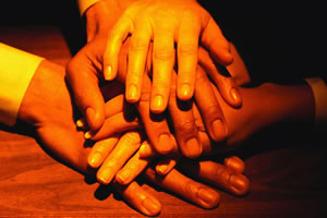 Photo: hands in a pile showing unity